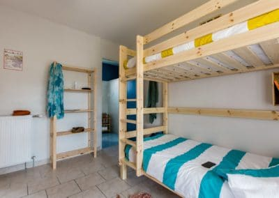 room with wood bunk-bed and a wood shelf