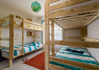 bright bedroom with 2 wood bunk beds and a red carpet
