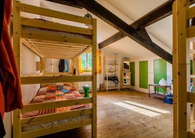 Bright attic bedroom with a wood bunk bed, a wood shelf and green closets