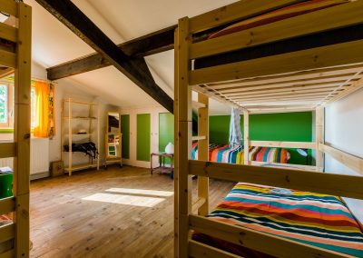 Bright bedroom with a wood bunk bed and a single bed, a wood shelf and green closets