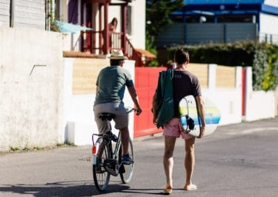 2 guys in the street: one biking, the other holding a surfboard and walking next to him