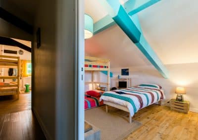 view from a corridor of 2 bedrooms with bunk beds