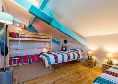 bright nice bedroom with a wood bunk bed and 2 single beds
