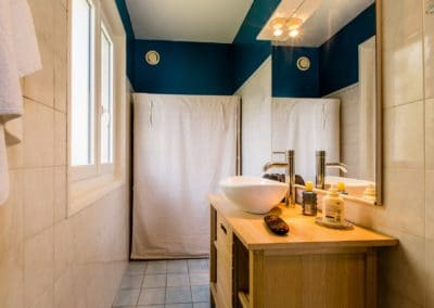 Blue bathroom with sink on a wooden piece of furniture and wardrobe hidden by a white curtain