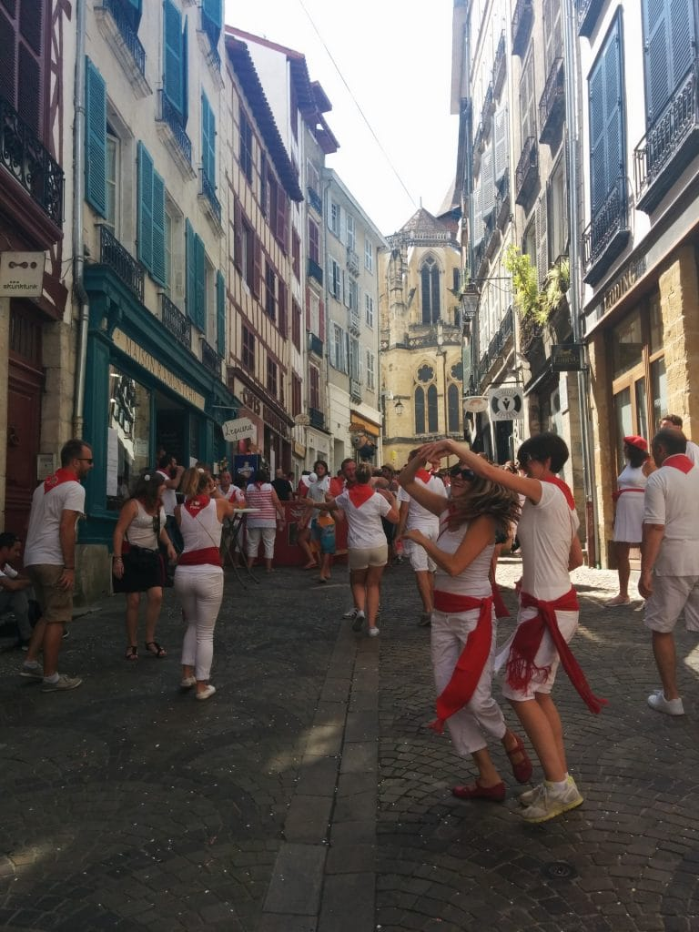 Festivaliers en rouge et blanc dansent dans la rue durant les fetes de Bayonne