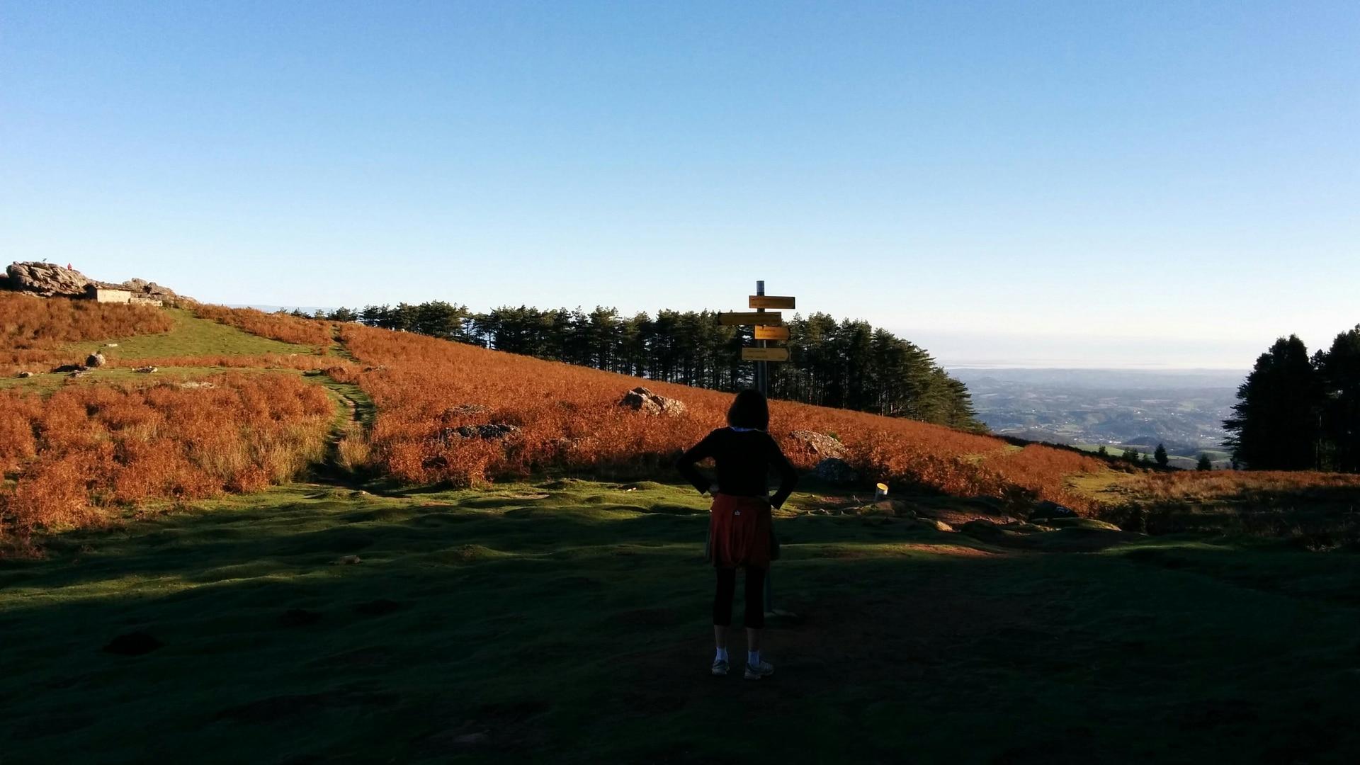 Jeune fille hésitant devant un panneau lors d'une randonnée en montagne