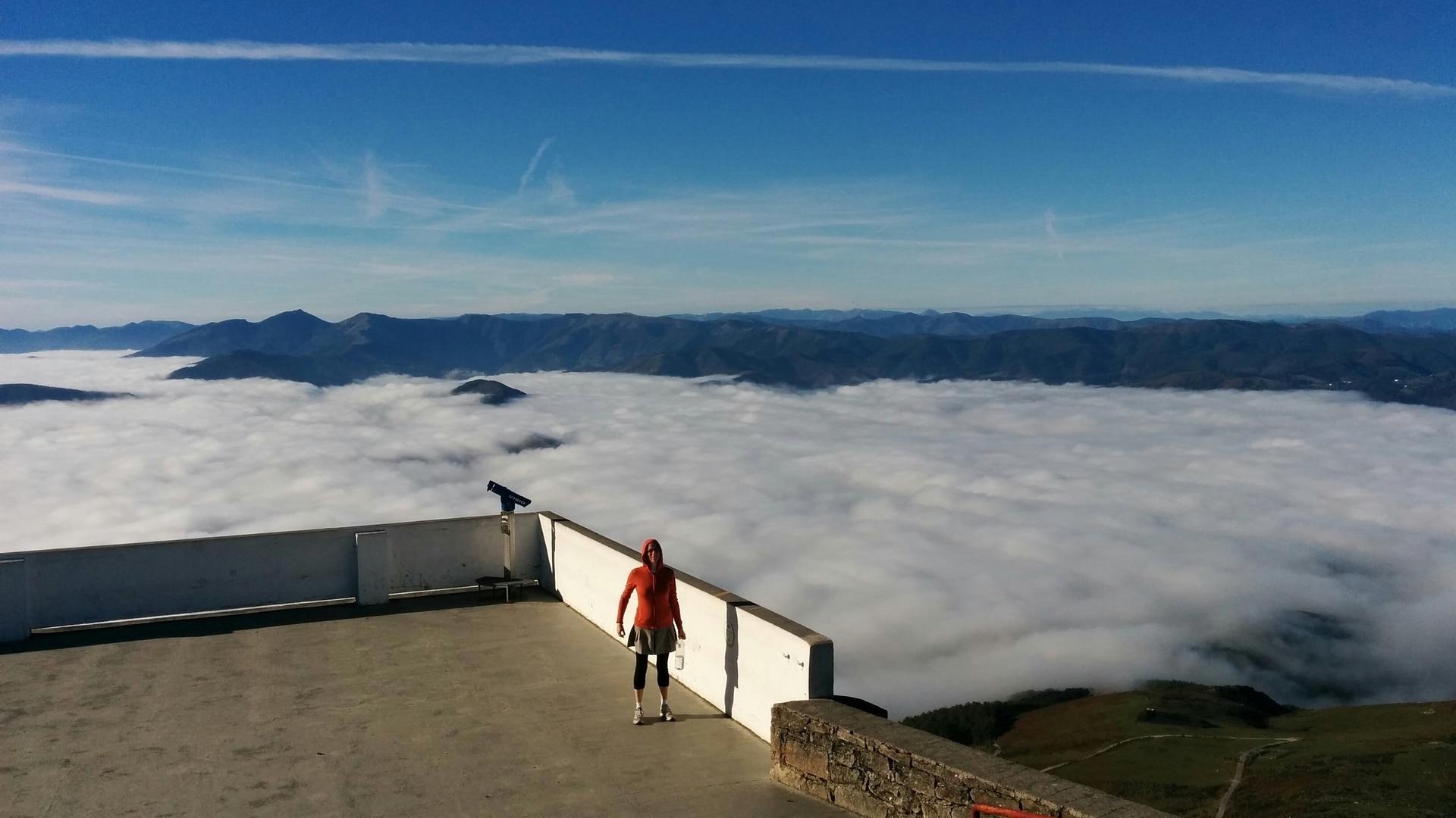 Jeune fille sur une plateforme au sommet d'une montagne surplombant une mer de nuages
