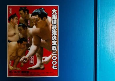 Red poster with sumo wrestlers on a blue door