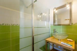 green modern bathroom with shower, glass sink and bamboo furniture item