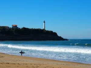 surfer with his board and biarritz lighthouse at petite chambre d'amour beach in anglet