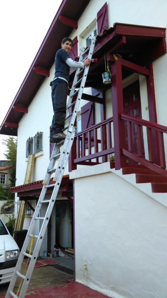 guyl standing on a ladder to paint outdoor woodwork in red