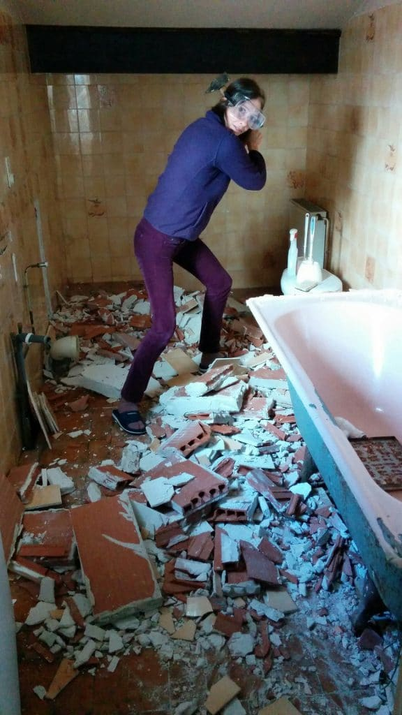 girl with a hammer destroying the bathtub of an old bathroom