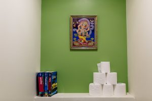 green wall of toilet with ganesh painting and guide books