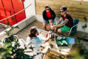 3 guys sharing a drink on a wood patio with wood pallet outdoor table
