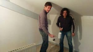 two nami house friends painting a room in white