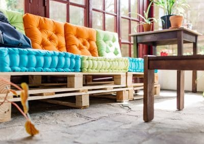 wood pallet sofa with blue, green and orange cushions