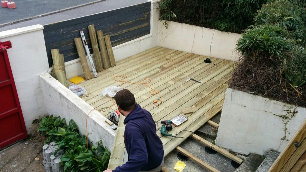 Worker finishing building a wood patio