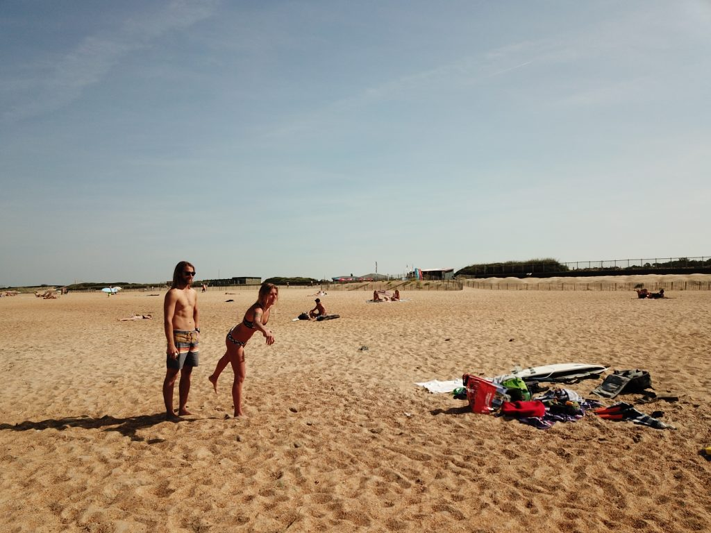 young couple playing petanque on the beach in Anglet
