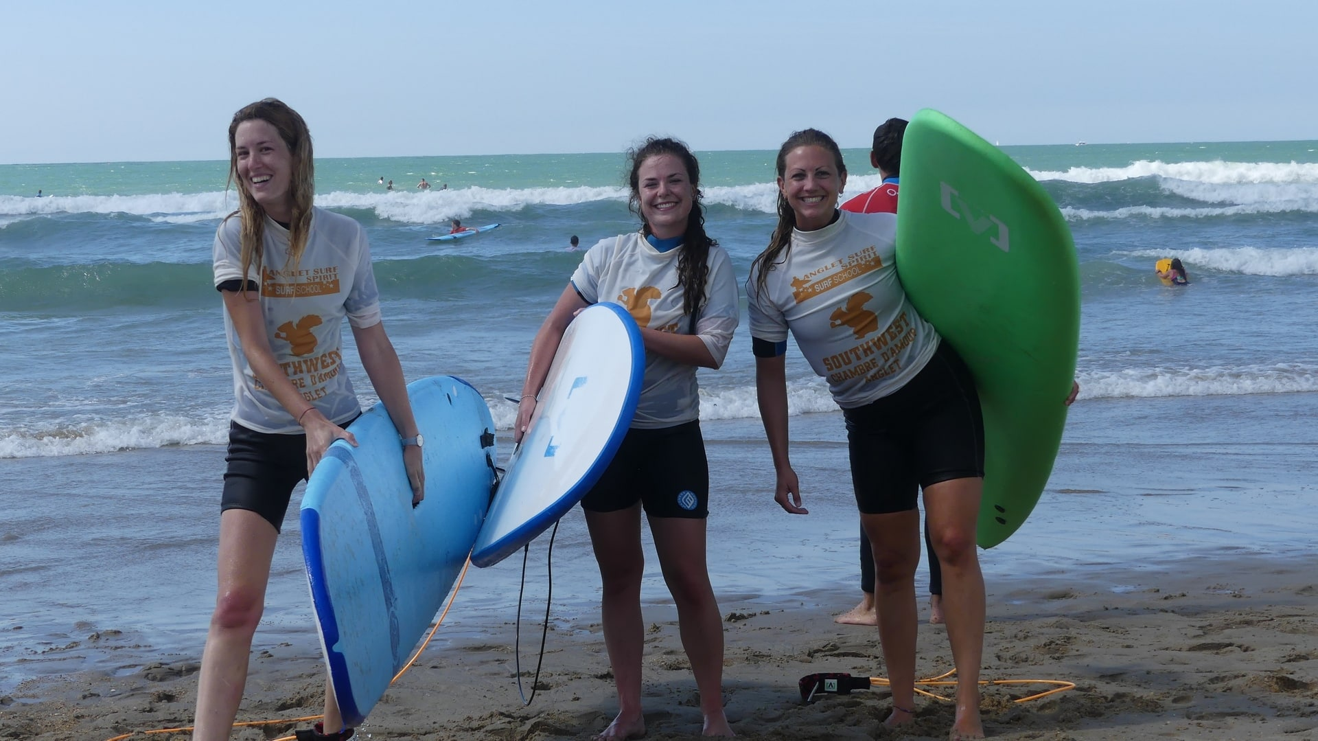3 girls with surfboards in front of the ocean in Anglet