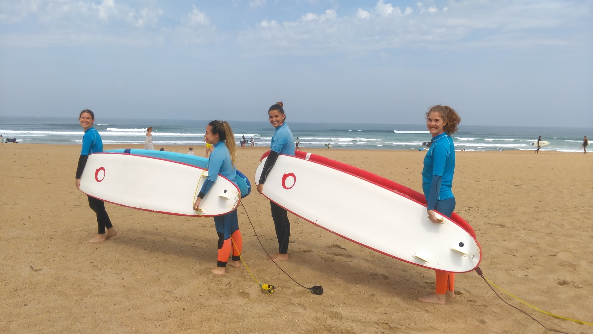 4 girls carrying surfboards on the beach