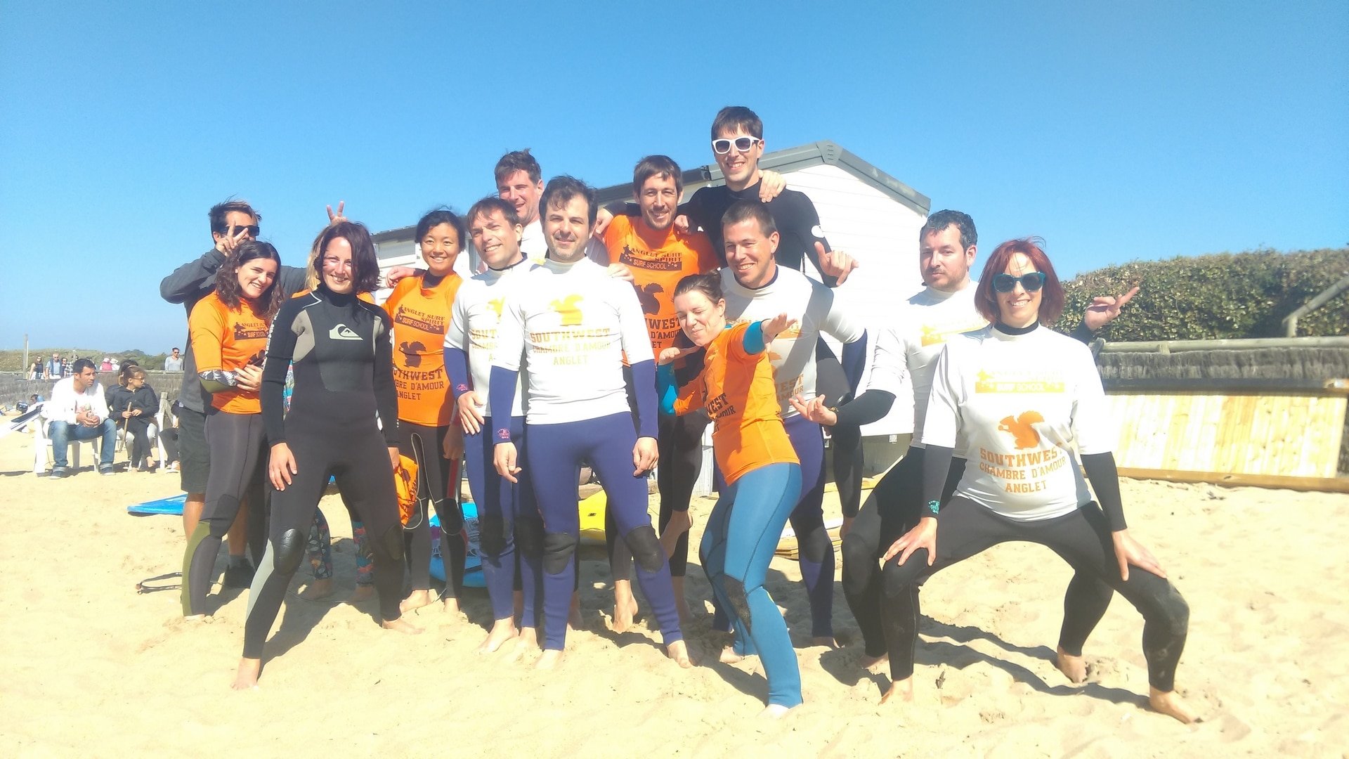 group of young guys and girls on the beach before a surf class