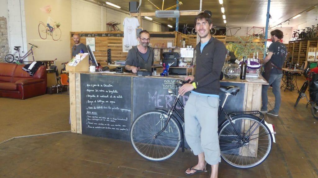 Clement de Nami House avec son vélo dans l'atelier de réparation de vélos