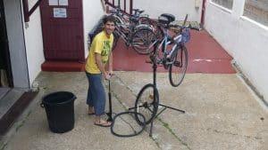 Clement repare un pneu de velo dans la cour de nami house