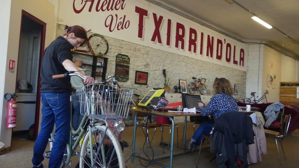 Jeune fille faisant marquer son vélo dans un atelier de réparation de vélo
