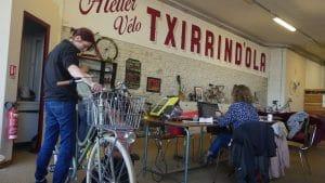 Fanny avec son velo dans l'atelier de reparation de velo