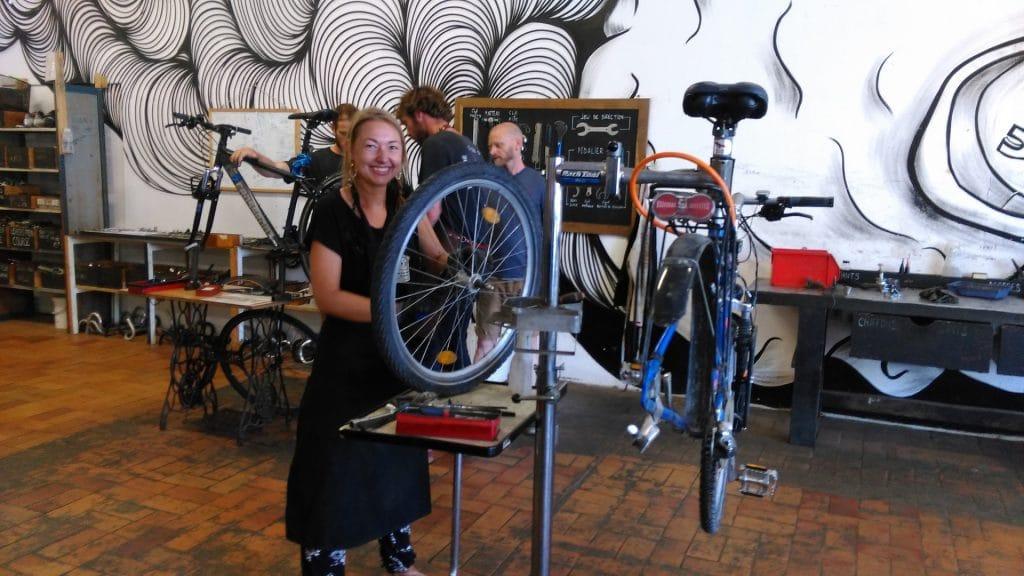 Smiling girl repairing her bike in a workshop