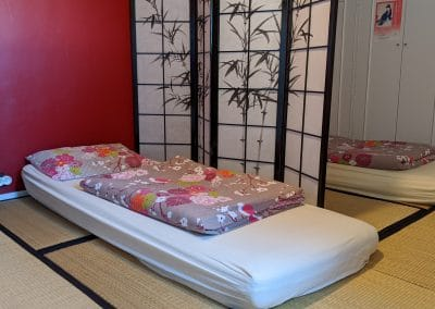 Japanese style bedroom with tatami mats and 2 futons separated by a traditional Japanese divider