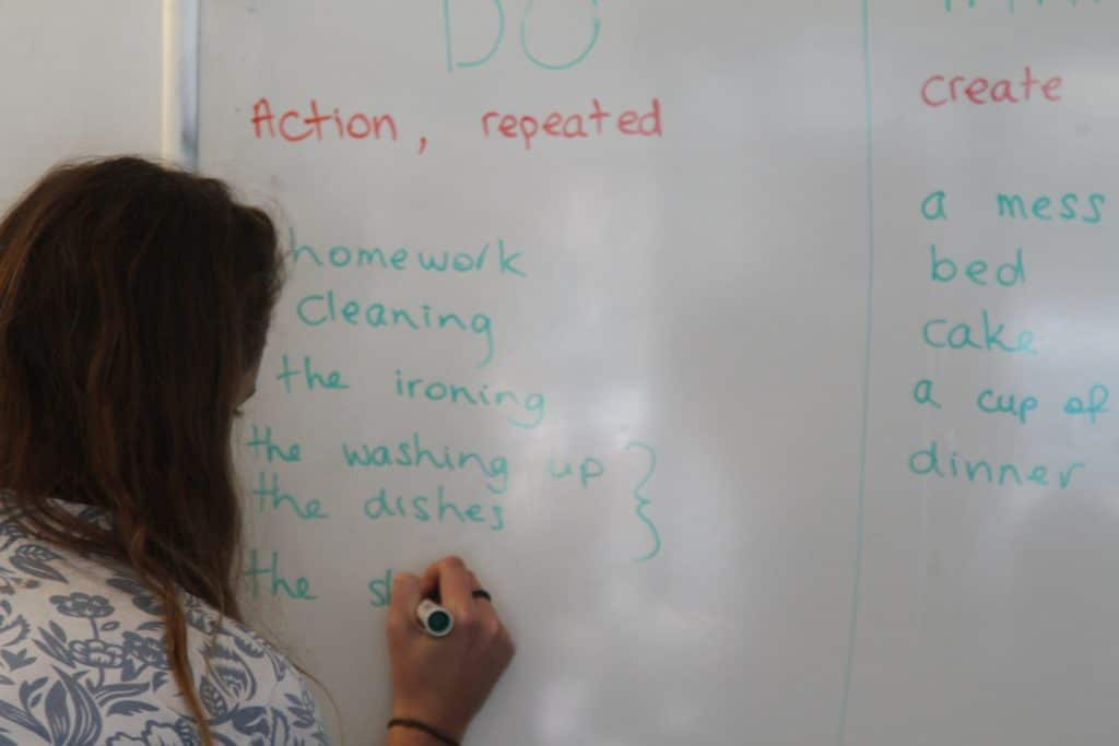girl writing on a white board during english class