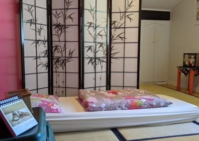 japanese style bedroom with tatami mats, futon and a traditional japanese divider